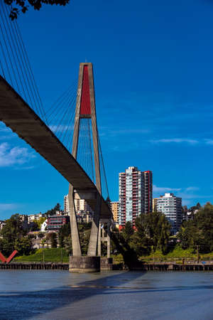 Sky-train bridge linking Surrey and New Westminster over the Fraser River, city on the opposite bank, blue sky with white clouds on a background