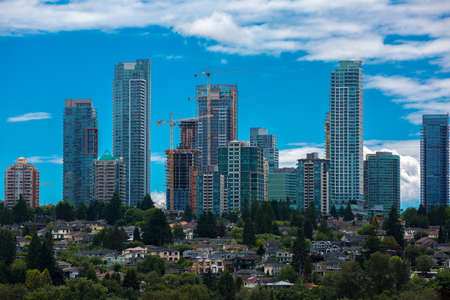 Construction of New Residential District  in the city of Burnaby, high-rise buildings under construction and construction cranes  against the backdrop of  blue cloudy sky and village in the foreground