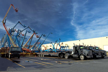 Construction machinery for rent. Lifts with raised platforms and cargo trucks are at the industrial court yard