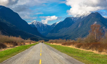 A country road in the Pitt River Valley runs through farm fields and forest to  Pitt Lake on the background of the snow-covered mountain range and a beautiful cloudy sky