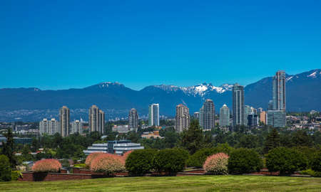 New residential area of high-rise buildings in the city of Burnaby, construction site in the center of the city against the backdrop of snow covered mountain range and blue sky