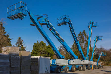 Construction machinery for rent. Lifts with raised platforms and are at the industrial court yard Archivio Fotografico