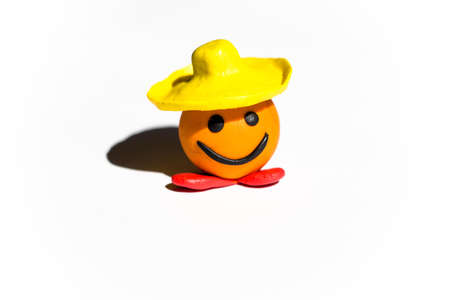 A round fairy-tale character is made of plasticine of different colors in a hat called Kolobok Stock Photo