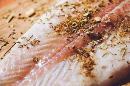 Fresh fish Pangasius is sprinkled with a variety of flavored spices and is ready for roasting. Stock Photo