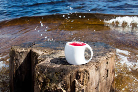 A cup of hot tea against the background of a lake and splashing waves in the early morning on the lake shore