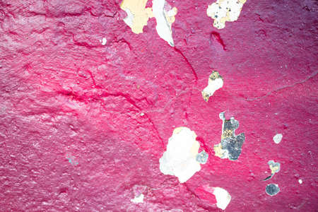 The texture of a red shade of cracked paint on a concrete wall