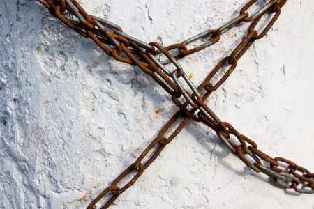 A long chain made of metal is covered with a little rust wrapped around the concrete wall and prohibits any movement. Indicates any prohibitions or dependencies. 写真素材