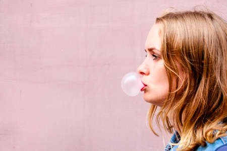 A beautiful girl on an isolated background of a pink tint stands in a profile and puffs a ball of a chewing gum. The bubble turned out great. Banco de Imagens