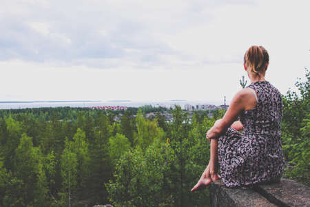 A young girl in a dress sits on a rock ledge above the forest, which is located on the shore of a huge lake. From the height you can see the spacious sky, houses, islands and the lake. Stock fotó