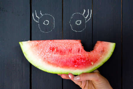 A piece of a bitten and juicy watermelon on a background of a wooden surface of black color. On the surface are painted eyes, in combination with a watermelon you get a funny face.