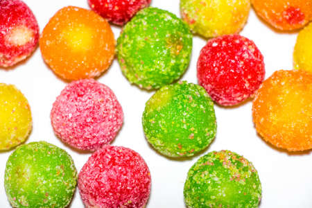 Several sweet and tasty round shaped candies are on a white background. They are sprinkled with sugar and look very appetizing.