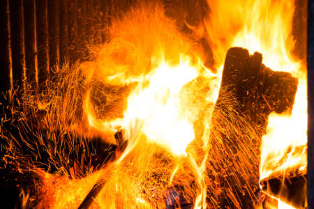 Firewood in the stove for heating. Sparks from the fire rise up. The temperature of the planet is very high. Stockfoto