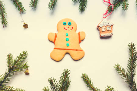Delicious baked gingerbread man lies on a white background. Around it are small golden bells and a gingerbread house. Great atmosphere of Christmas and New Year.