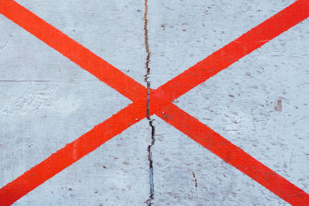 The lines are painted on a wooden surface. The lines of intersect and create a cross. The intersection of the lines.