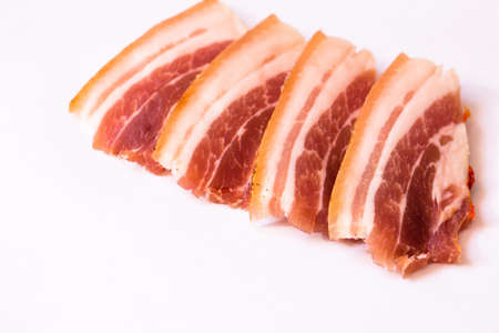 Bacon slices on a white neutral background. Bacon is ready for use. Foto de archivo - 121916134
