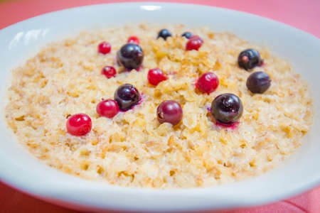 Tasty buckwheat porridge with milk and berries. Blueberries and cranberries are very good for health.
