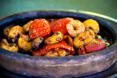 Tasty fried prawns with tomatoes and peppers. Vegetables and vegetables. The dish is served in clay dishes.
