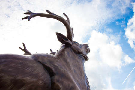 A large deer is made of wood against the sky. The deer has large horns that, against the sky, seem to touch the clouds. The head of a deer is raised to the sky.