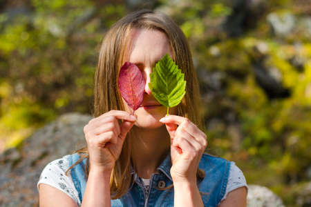 Beautiful and young girl holds leaves. With leaves, she closed her eyes. A girl stands on a background of nature. Banco de Imagens