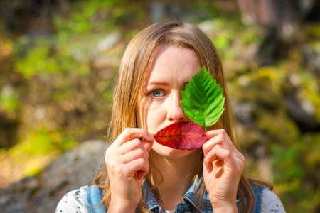 Beautiful and young girl holds leaves. With leaves, she covered one eye and her delicate lips. A girl stands on a background of nature.