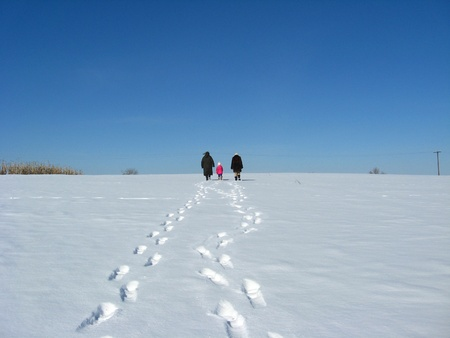 Outgoing people and traces on a snow photo