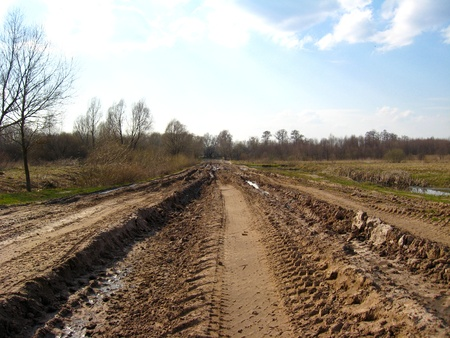 the image of rural road with greater traces of cars and a dirt photo