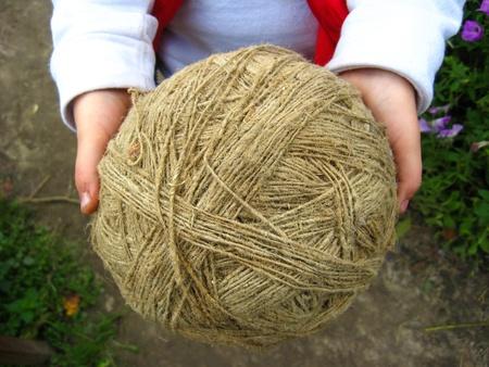het beeld van de grote kluwen van vlasvezels in handen