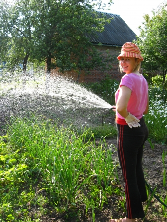 The girl watering a kitchen garden in the country photo