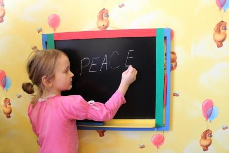 Het meisje schrijft op een schoolbord een woord van de vrede