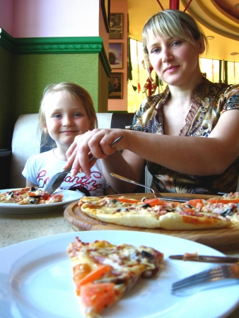 Happy and smiling mother and her child in pizzeria