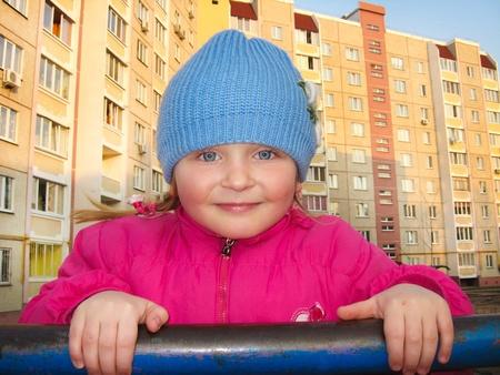 rekstok: De blue-eyed girl op een horizontale balk op een achtergrond van de multi-verdiepingen tellende huis Stockfoto