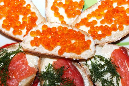 a lot of sandwiches with red caviar and red fish photo