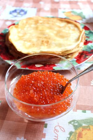 red caviar in a plate with the spoon and pancakes on a background photo
