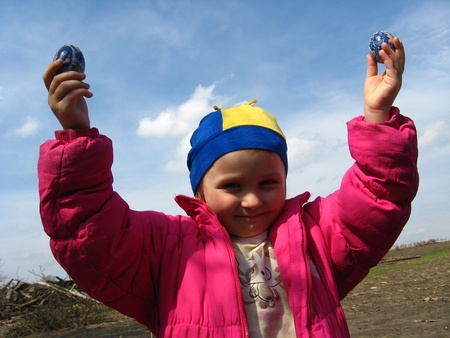 image of little girl with Easter eggs on a background of the blue sky photo