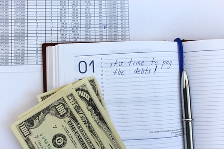 writing down in a notebook about a debt and american dollars Stock Photo - 19118428