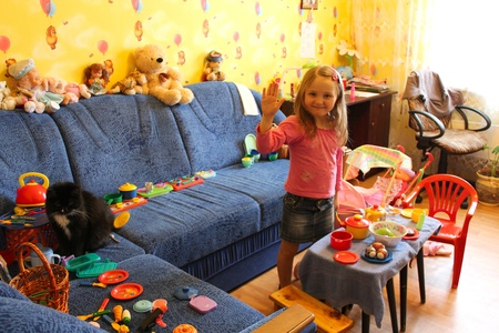 little girl playing with toys and cat in her room photo