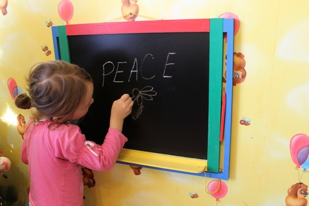 little girl writes on blackboard word Peace photo