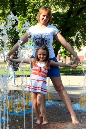 image of mother and daughter dancing in the fountains photo