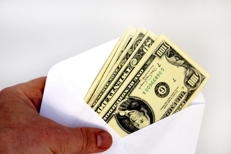 windfall: hand holding dollar banknotes in envelope as a bribe isolated on a white background