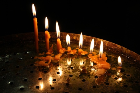 image of row bright burning church candles on candlesticks