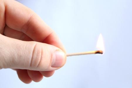 het beeld van de hand met brandende match
