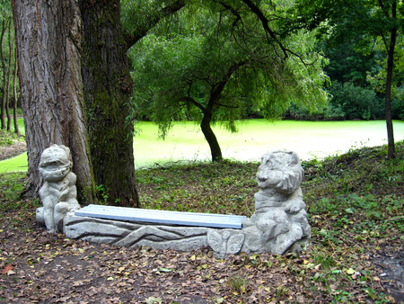 Original bench with figures in the park with lake photo
