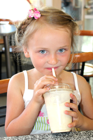 little beautiful girl drinking tasty cocktail in fastfood Stock Photo - 23222923