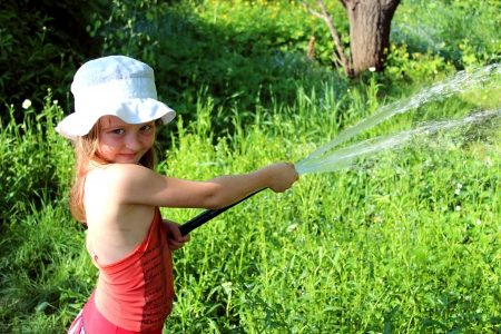 watered: girl watering a kitchen garden in the country Stock Photo