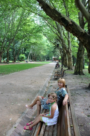 mother and daughter sitting on the bench in park with greater trees photo