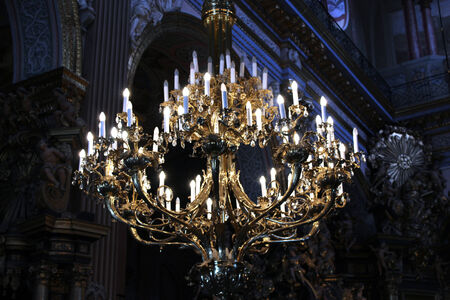 Beautiful chandelier with many candles under the church top