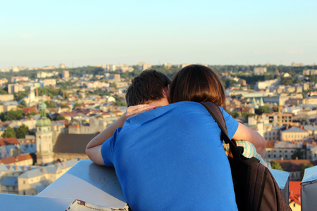 amorousness: Pair of young enamoured people on a background of house-tops of Lvov