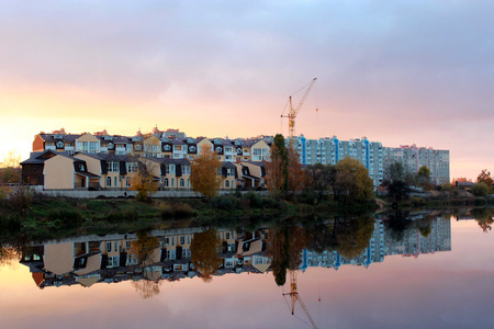 beautiful landscape with sunset, river and modern house reflecting in it Stock Photo