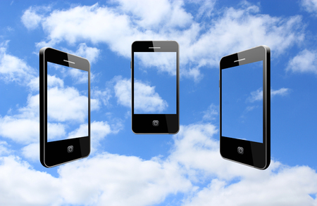 three modern mobile phones on the cloudy sky photo