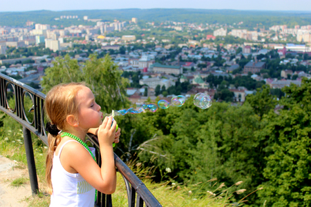 little girl swelling soap big bubbles out of city photo